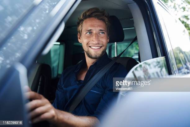 smiling young man in car - auto stockfoto's en -beelden