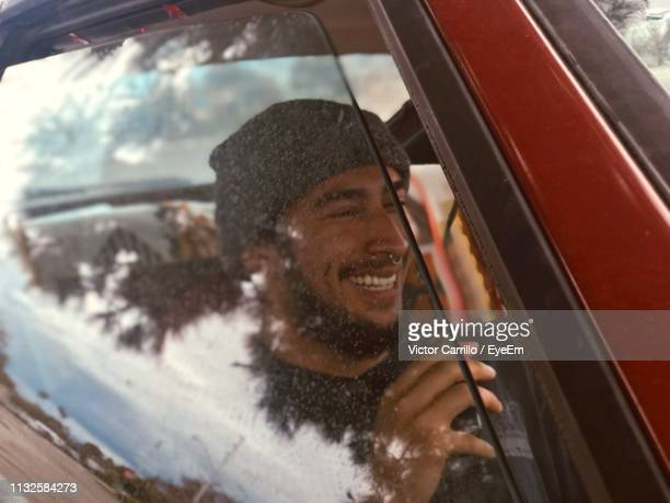 smiling young man in car seen through window - san leandro stock photos and pictures