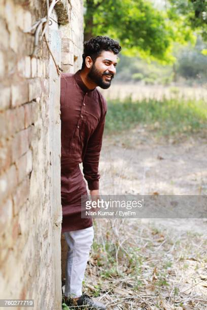 smiling young man in kurta looking away while standing by wall on field - kurta stock pictures, royalty-free photos & images