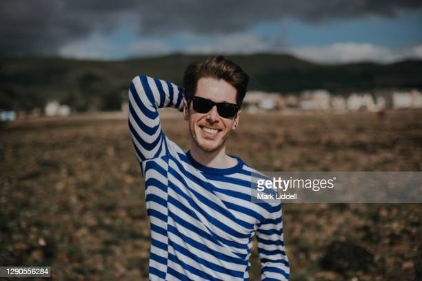 smiling young man in striped sweater standing on the beach, largs, scotland - river clyde stock pictures, royalty-free photos & images