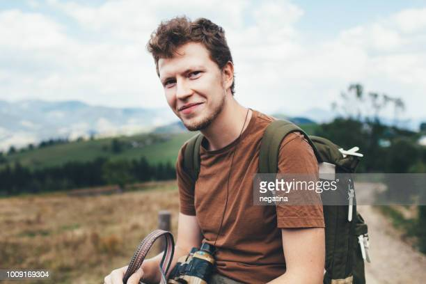 smiling young man in the brown t-shirt with green backpack and binoculars in the mountains - europa oriental - fotografias e filmes do acervo