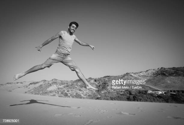Smiling Young Man Jumping On Beach Against Clear Sky