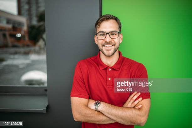 giovane sorridente appoggiato al muro verde - maglietta polo foto e immagini stock