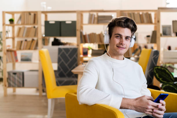 Smiling young man listening music through headphones while holding mobile phone in new home