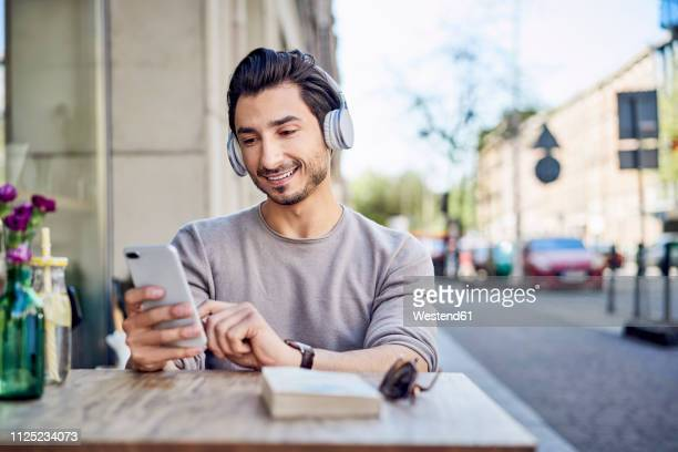 smiling young man listening to music on headphones at outdoors cafe - pavement cafe stock pictures, royalty-free photos & images