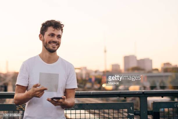 smiling young man looking away while holding mobile phone on bridge against clear sky during sunset - europäischer abstammung stock-fotos und bilder