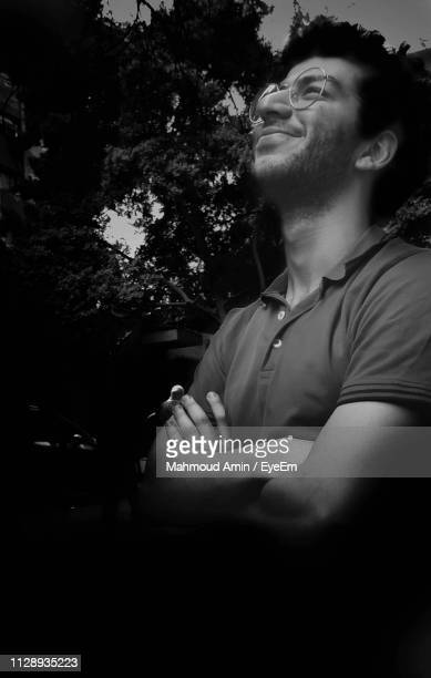 Smiling Young Man Looking Away While Sitting Against Tree