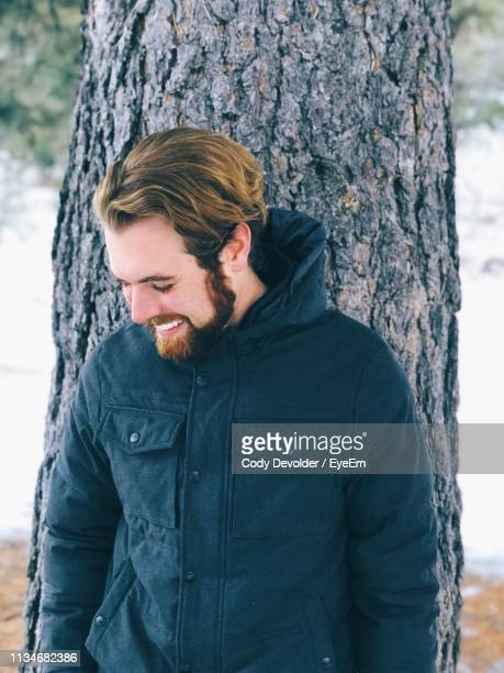 Smiling Young Man Looking Down While Standing Against Tree Trunk
