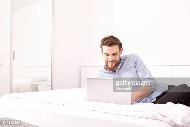 Smiling young man lying on a hotel bed using laptop