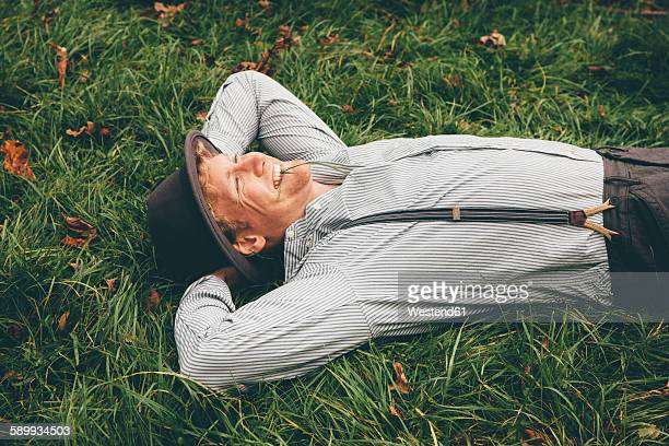 smiling young man lying on a meadow with hands behind his head - サスペンダー ストックフォトと画像
