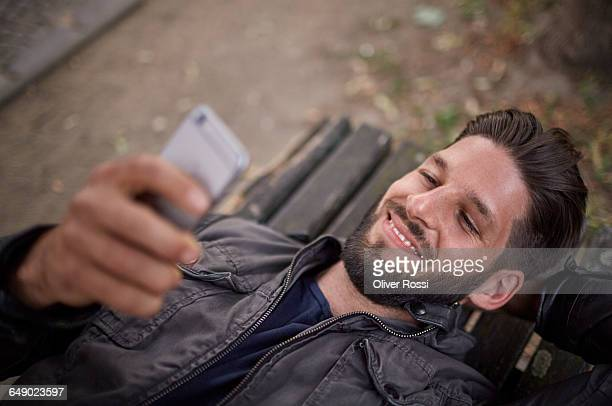 Smiling young man lying on bench with cell phone