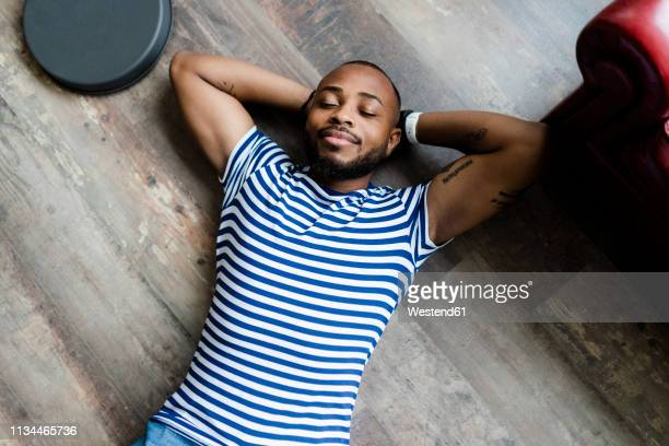 smiling young man lying on wooden floor with closed eyes - lying down stock pictures, royalty-free photos & images
