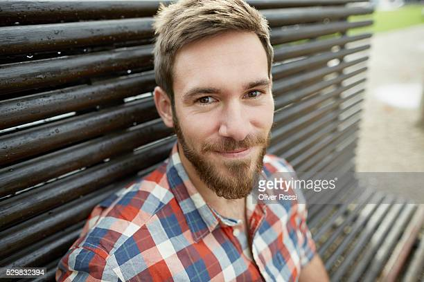 Smiling young man on bench, portrait