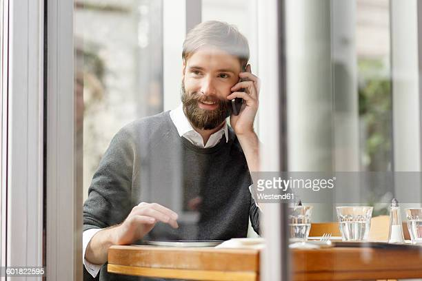 Smiling young man on cell phone in restaurant
