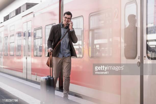 smiling young man on cell phone walking on station platform along commuter train - bahnreisender stock-fotos und bilder
