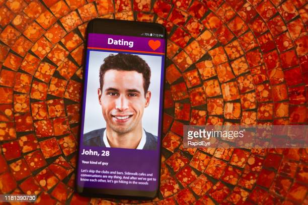 smiling young man on mobile phone dating app - online dating stock pictures, royalty-free photos & images