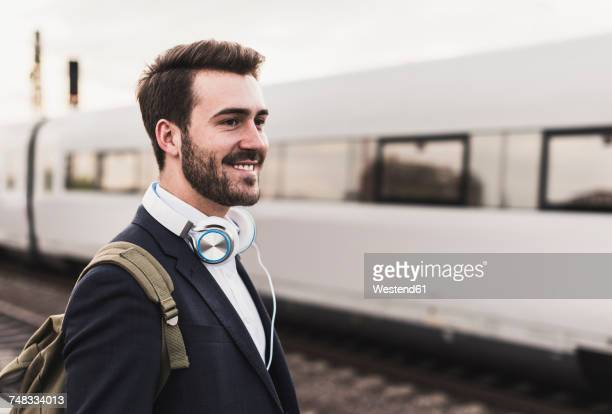 Smiling young man on platform as train coming in