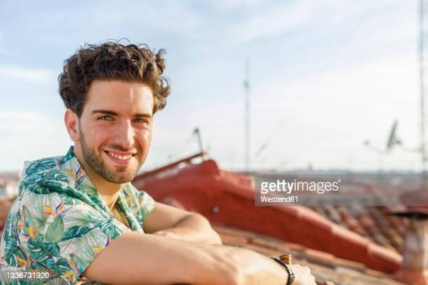 smiling young man on terrace during weekend - sorriso aberto imagens e fotografias de stock