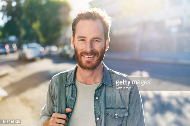 smiling young man on the street - hommes photos et images de collection