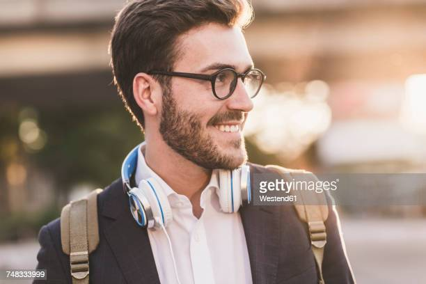 Smiling young man outdoors looking sideways
