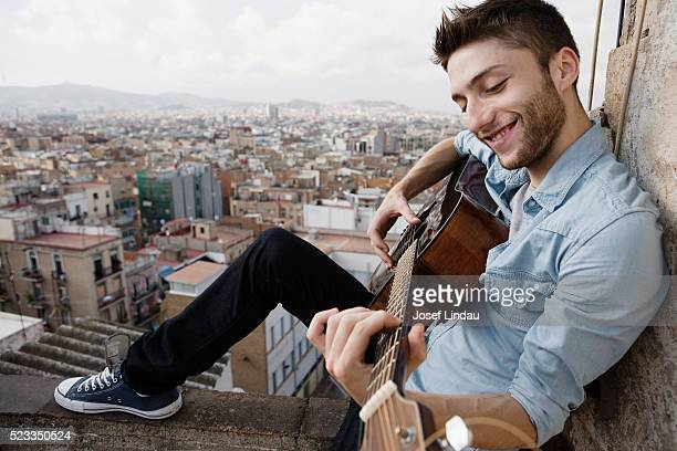 Smiling young man playing acoustic guitar