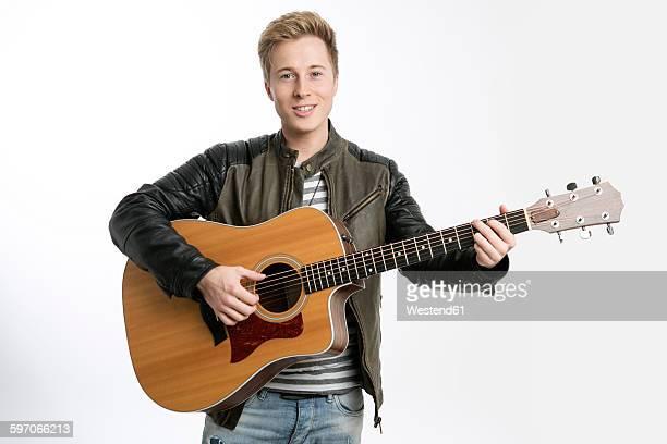 Smiling young man playing guitar