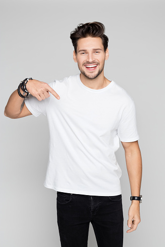 Smiling young man pointing down 996927722