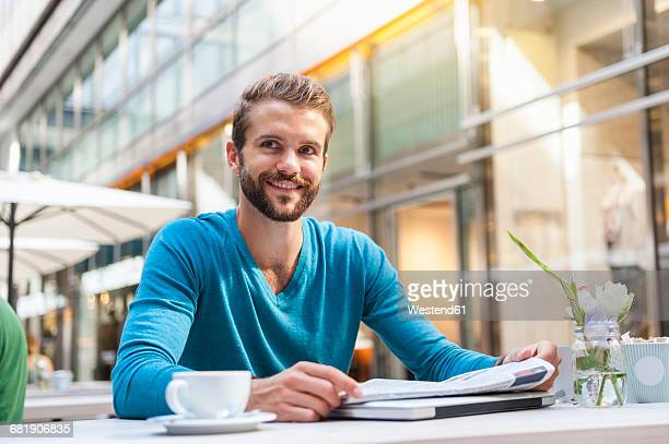 Smiling young man reading newspaper in a cafe