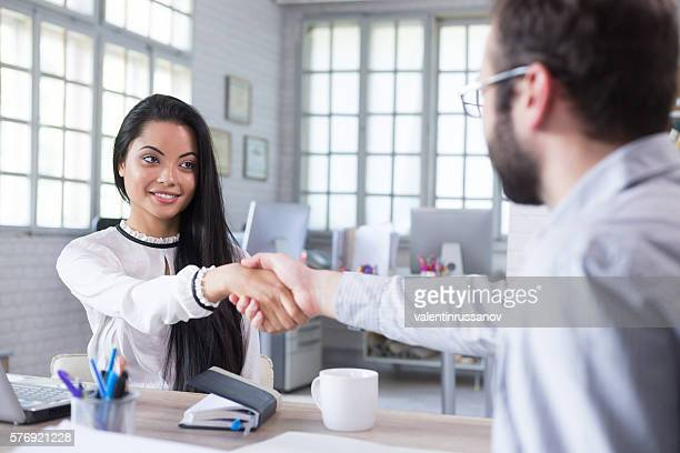Smiling young man recieves documents at the office