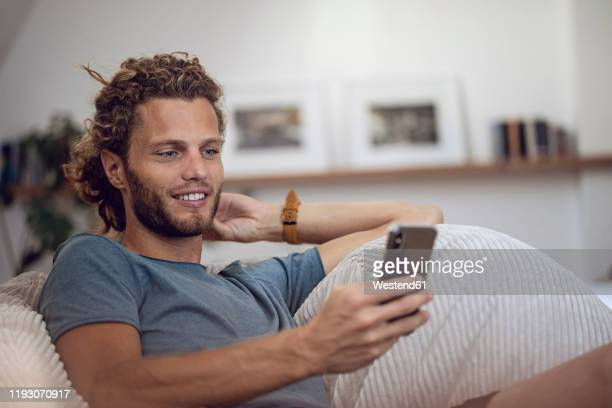 smiling young man relaxing in beanbag at home using cell phone - one young man only ストックフォトと画像
