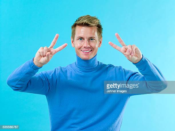 Smiling young man showing victory sign
