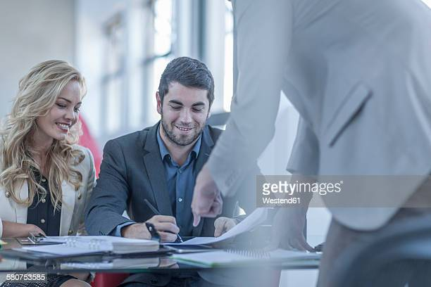 Smiling young man signing a contract