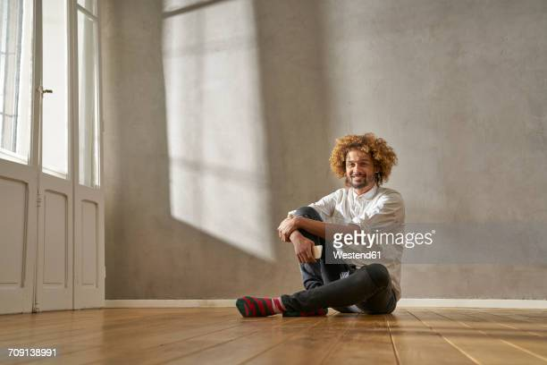 smiling young man sitting in a room - sitting stock-fotos und bilder
