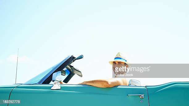 Lächelnder, junger Mann sitzt im Auto-copyspace