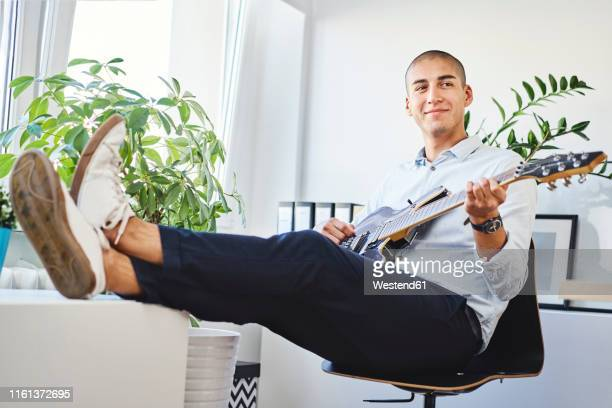 smiling young man sitting in home office and playing the guitar - electric guitar stock pictures, royalty-free photos & images