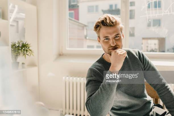 smiling young man sitting in office, hand on chin - casual clothing stock-fotos und bilder