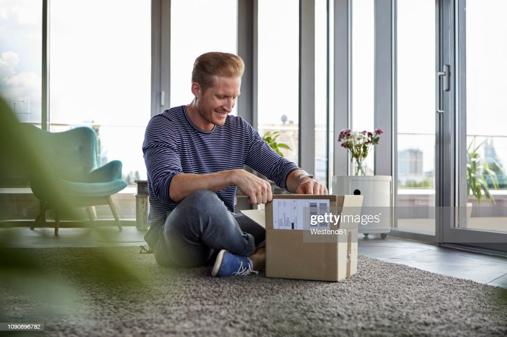 Smiling young man sitting on carpet at home unpacking parcel : Photo