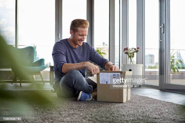 smiling young man sitting on carpet at home unpacking parcel - ein mann allein stock-fotos und bilder