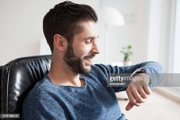 Smiling young man sitting on leather chair looking at his smartwatch