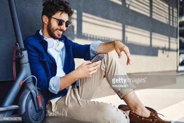 smiling young man sitting on the ground besides his electric scooter using cell phone - electrical equipment stock photos and pictures
