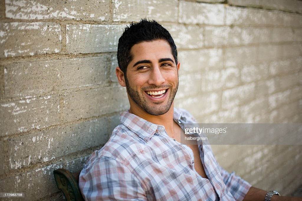 Smiling Young Man Sitting Outside : Stock Photo