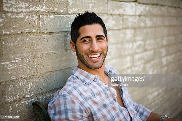 smiling young man sitting outside - persian stock photos and pictures