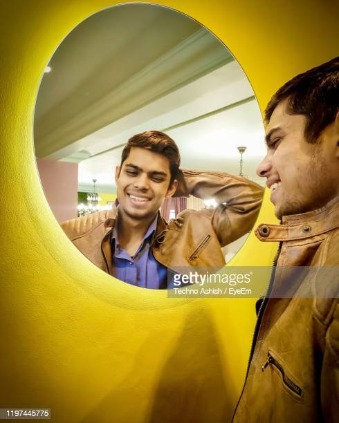smiling young man standing in front of mirror - in front of stock pictures, royalty-free photos & images