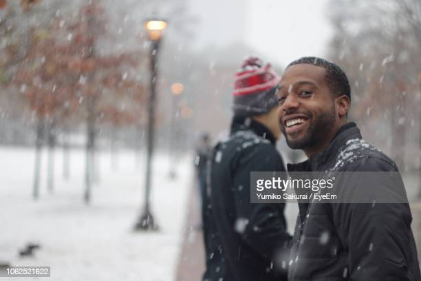 Smiling Young Man Standing In Park During Snowfall