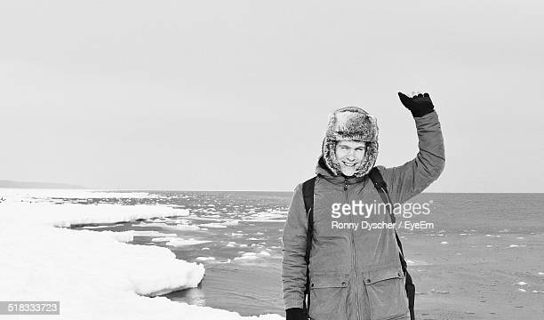 Smiling Young Man Standing On Snowy Shore
