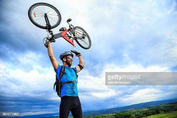 Smiling young man standing on top and lifting his bike