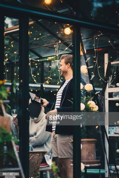 Smiling young man standing with digital tablet by woman at dining table during garden dinner party