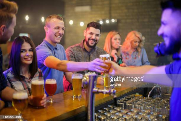 smiling young man taking a glass of beer from the bartender - passing giving stock pictures, royalty-free photos & images