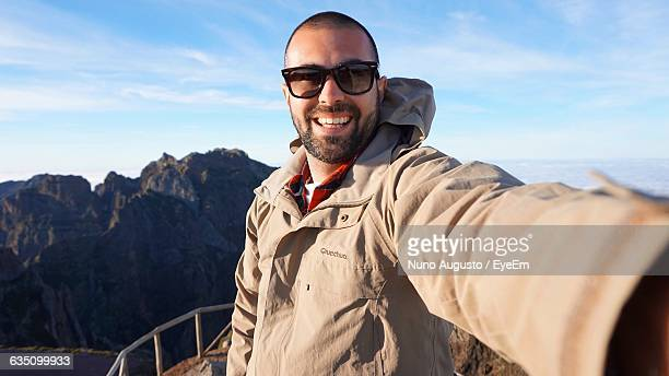 Smiling Young Man Taking Selfie While Standing By Mountain Against Sky