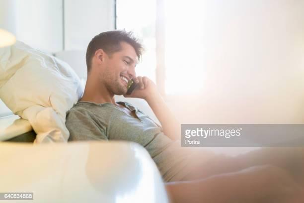 Lächelnder junge Mann telefonieren mit Handy zu Hause